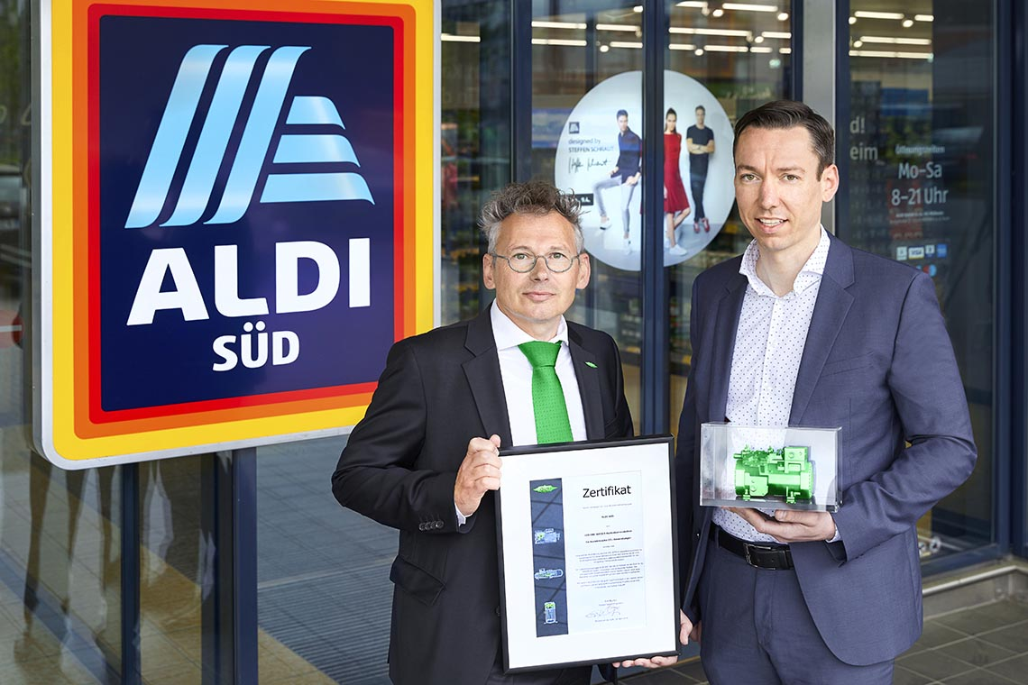 Erik Bucher, Director Sales Refrigeration at BITZER (left), presenting the model of a reciprocating compressor and a certificate to Jens Straßburg, Director Store Operations Management Refrigeration at ALDI SÜD