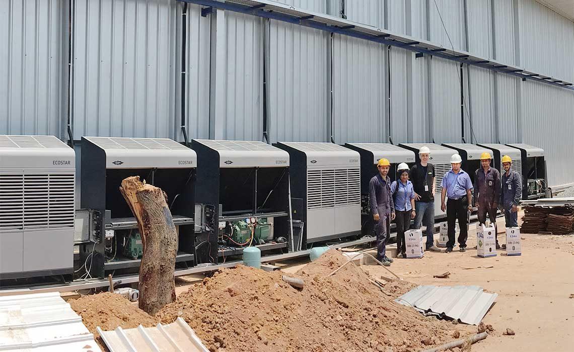 Mitarbeiter des Projekts stehen vor den Verflüssigungssätzen mit der großen Lagerhallte im Hintergrund
