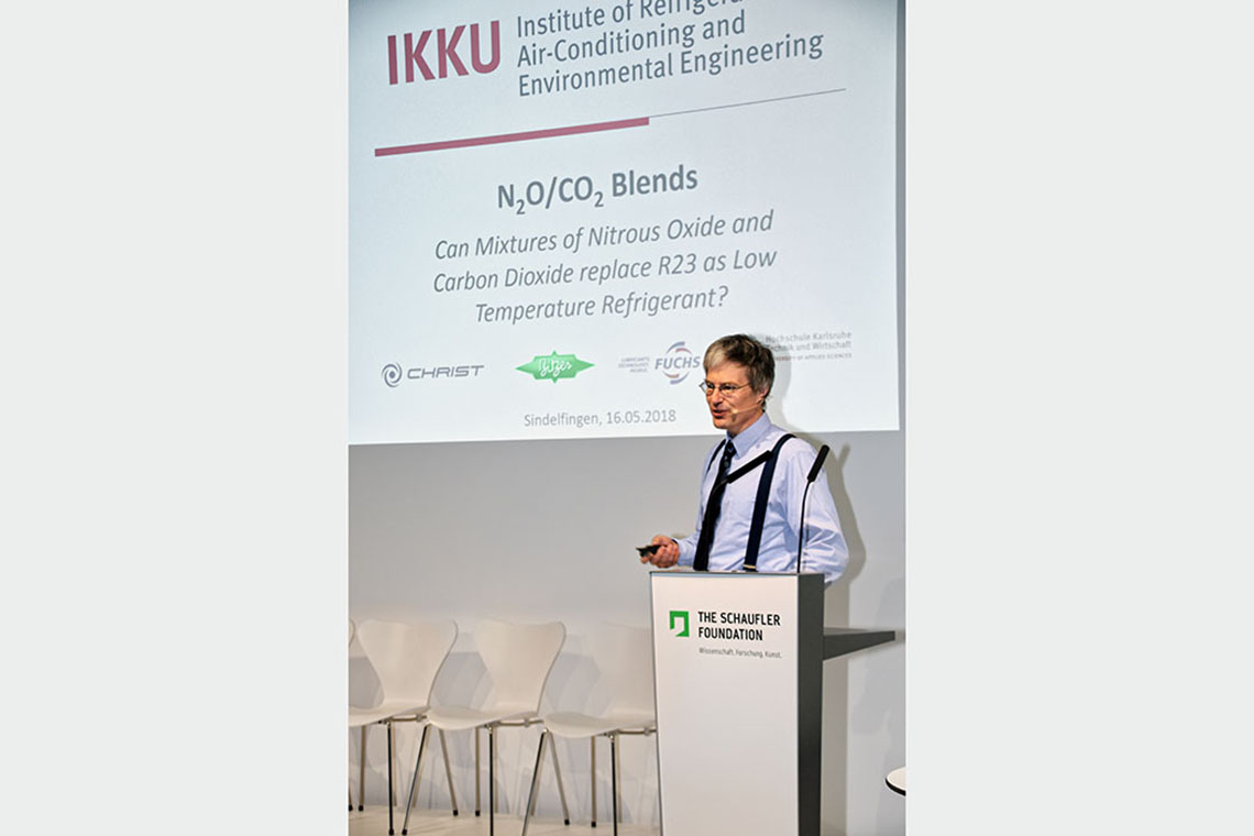 "Prof. Dr. Michael Kauffeld, Speaker of the Institute of Refrigeration, Air-Conditioning, and Environmental Technology at Karlsruhe University of Applied Sciences, during his speech on the podium about ""N₂O/CO₂ Blends"""
